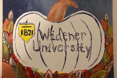 Painting of a pumpkin surrounded by leaves and 'Widener University' and the shield in the center