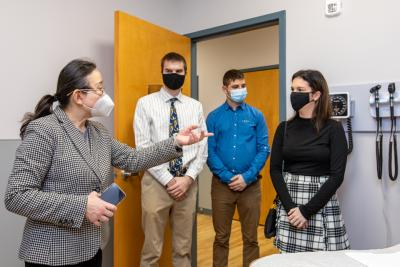 Doctor talks to three students in medical facility